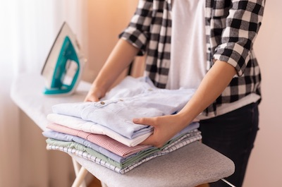 Holding folded shirts on an ironing board.