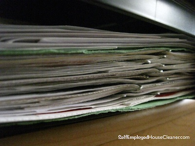 A stack of cleaning business start-up papers in a folder.